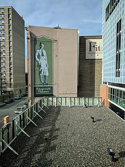 A mural depicting Fitzgerald in Saint Paul, Minnesota Downtown Saint Paul roof with Fitzgerald Theater mural in background.jpg