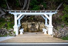 A white, flat-roofed gazebo over a spring, with a plaque located on a rock next to the spring. A short, wide wooden walkway leads from the road to the gazebo.