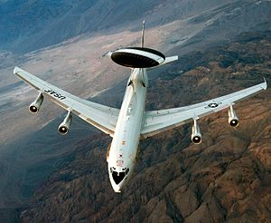 Aerial view port view of white jet aircraft in-flight. It has a large disc-like black radar lying horizontally above two convergent struts.