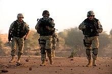 Photographie de soldats polonais au Tchad avec leur véhicule de transport blindé.