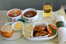 Business class meal. Cloth-covered tray with napkin, tall glass, two round bowls with fruits and chocolate cake; plate with bread and butter, large dish with potatoes, meat, and vegetables.