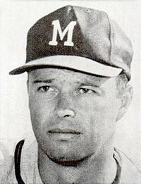 "Bust portrait of a man in a white jersey with a dark stripe around the neck. He is wearing a dark baseball cap with a white ""M"" on it."
