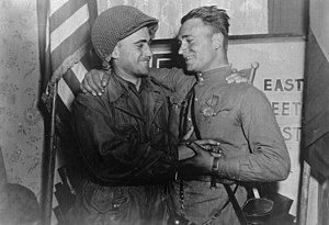 Elbe Day - In an arranged photo commemorating the meeting of the Soviet and American armies, 2nd Lt. William Robertson (U.S. Army) and Lt. Alexander Silvashko (Red Army) stand facing one another with hands clasped and arms around each other's shoulders. In the background are two flags and a poster.