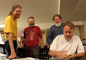 Erik Demaine - Erik Demaine (left), Martin Demaine (center), and Bill Spight (right) watch John Horton Conway demonstrate a card trick (June 2005)
