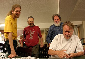 Erik Demaine - Erik Demaine (left), Martin Demaine (center), and Bill Spight (right) watch John Horton Conway demonstrate a card trick (June 2005)