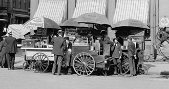 "Hot dog - Carts selling frankfurters in New York City, circa 1906. The price is listed as ""3 cents each or 2 for 5 cents""."