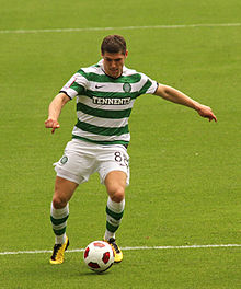 A colour photograph of a footballer, wearing a green-and-white hooped shirt and socks with white shorts and yellow boots. He is controlling the football and preparing to take a shot.