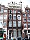 foto van Huis met gevel onder gebeeldhouwde lijst en attiek en twee zandstenen schoorstenen op het dwarse dak