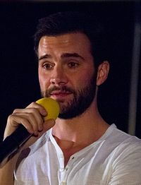 A 35-year old, dark-haired, bearded man, talking into a microphone and looking to the left of the camera.