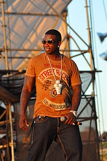 Gucci Mane performing in Williamsburg, Brooklyn on August 29, 2010. He is holding a microphone in his left hand and is wearing his signature ice cream cone medallion.
