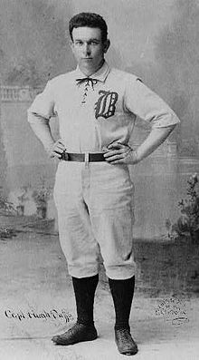 Portrait of a man in a white baseball uniform.