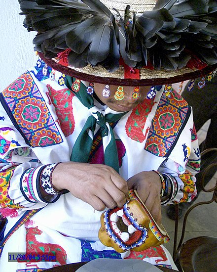 A Wixarika man making a beaded jaguar head Huichol Trabajando.JPG