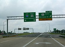 Two green signs are located above an elevated portion of roadway with no traffic visible on a cloudy day.