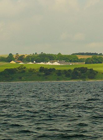 Isgård -  Isgård viewed from Begtrup Vig (Begtrup Bay) with newer farm buildings specialized for breeding piglets in the foreground.