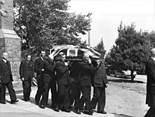 Black and white photo of a coffin which has been draped with a British flag being carried by pallbearers. The pallbearers are middle-aged men wearing formal suits, and three other middle aged men in suits are following the pallbearers.