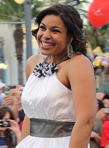 A white woman wearing a white dress, smiling.