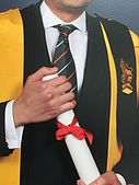 Individual holding a diploma, wearing an academic gown with a black epitoge over the left shoulder
