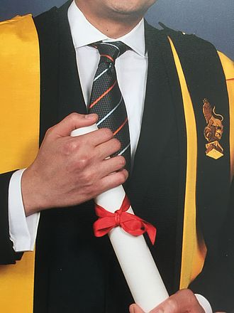 Academic dress of King's College London - Academic dress with the AKC epitoge buttoned to the shoulder, depicting Reggie the Lion