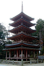 A five-storied pagoda with vermillion red beams and greenish roof. Just below the first-story roof there is an additional pent roof.