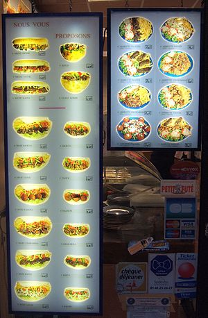 Menu - A lighted display board-style menu outside a French Kebab restaurant.
