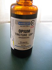 "Orange transparent bottle labelled ""opium tincture USP (deodorized)"". There is a warning label declaring the product to be poisonous."