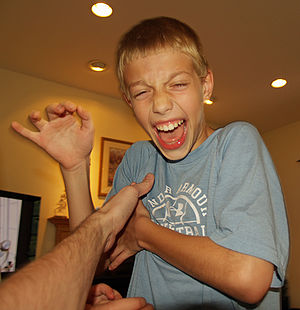 Haptic communication - A boy laughing as he is tickled looks close to tears