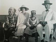 le roi et la reine en vêtements clairs posent assis sur un banc en compagnie de deux enfants
