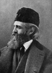 photo in profile of a man with a long beard, wearing a hat and an overcoat
