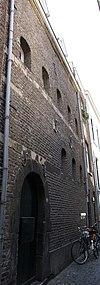 foto van Pakhuis, met in de lijstgevel een rondbogig poortje in Naamse steen en venstertjes met gedrukte bogen. Achtergevel aan de Waterpoort in dezelfde trant doch zonder poort.