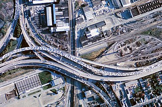 MacArthur Maze - Aerial view of the MacArthur Maze (early 1970s, prior to post-Loma Prieta rebuild); I-80 is the short curved segment in the upper left corner; I-580 runs east-west (left-right) through the center of the photograph, crossing the Southern Pacific tracks running north-south; and I-880 curves south onto the Cypress Street Viaduct at the bottom.