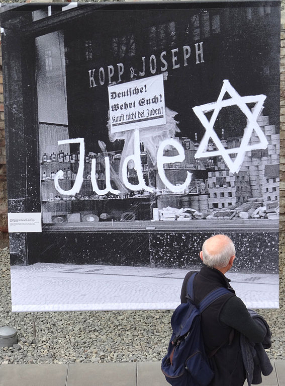 file man views photo of nazi boycotted jewish shop topography of terror outdoor exhibit. Black Bedroom Furniture Sets. Home Design Ideas