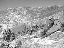 A line of soldiers on a hill under a boulder engaged in a battle