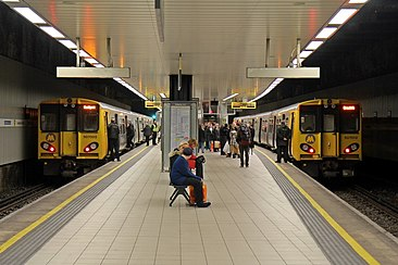 Two yellow trains on either side of a platform in an underground station