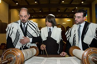 Rite of passage - Jewish boy reading a Torah scroll at his Bar Mitzvah, using a Yad