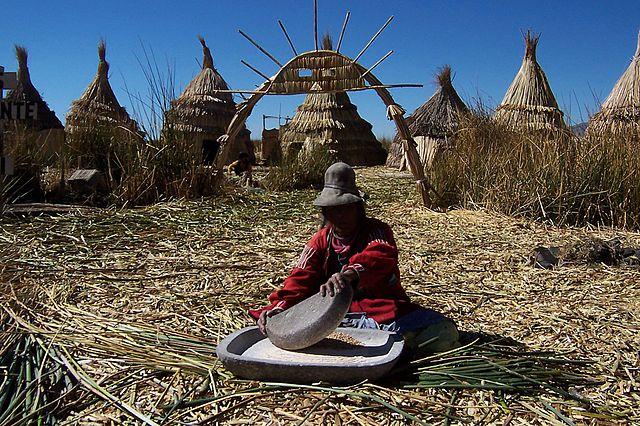Nativa de la etnia uros moliendo maíz. Las islas flotantes de los uros. Lago Titicaca. Perú