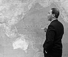 Middle-aged black-haired man, stands side-on in a dark suit with a cigarette in right hand and left hand in pocket, looking at the large map of the Asia Pacific region on the wall.