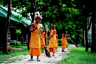 Samanera - Thai novices sweeping temple grounds.