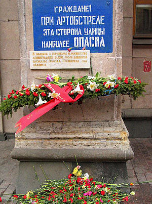 """Effect of the Siege of Leningrad on the city - This sign is located near the western end of Nevsky Prospekt and reads """"Citizens! During artillery bombardment this side of the street is especially dangerous"""". The white plaque reads """"In memory of the heroism and courage of the people of Leningrad during the 900-day siege of the city this inscription is preserved"""". The blue paint is refreshed every year on May 9"""