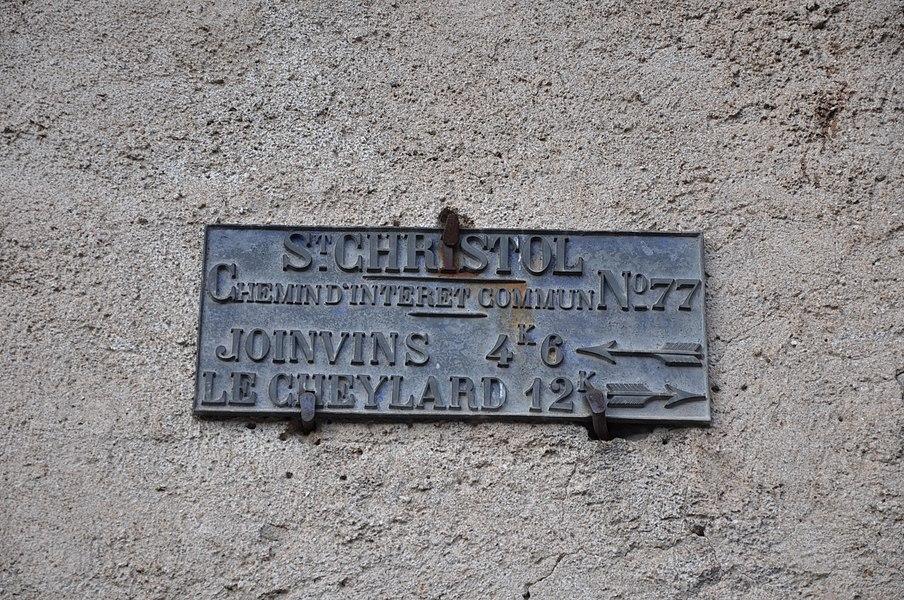 """Plaque d'indication à Saint-Christol. Est inscrit: St-Christol Chemin d'interet commun n°77 Joinvins 4,6 km à gauche  Le Cheylard 12 km à droite"""""""