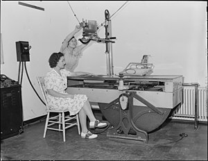 R.N., Hazel Jamison, adjusts the X-Ray machine...