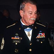 A gray-haired white man wearing a formal military uniform with a star-shaped medal hanging from a ribbon around his neck