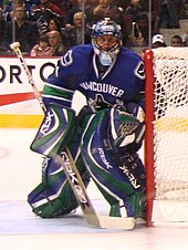 A masked ice hockey goaltender wearing a blue jersey with blue and green pads slightly crouched looking forward.