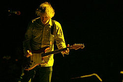 A man performing live on-stage, playing a red guitar. A yellow light shines on him.