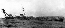 A large warship rolls onto its side.