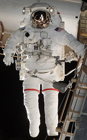 Extravehicular Mobility Unit - The Enhanced EMU Suit. The suits are white to reflect heat and to stand out against the blackness of space; the red stripes serve to differentiate astronauts.