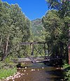A short dark metallic bridge with rectilinear and diagonal elements over a stream with woods on either side and a wooded mountain in the background