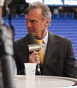 "A grey-haired man in a black suit and yellow tie looks to his right, a microphone marked ""MSG"" held to his mouth."