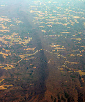 Sideling Hill - Oblique air photo of Sideling Hill, facing north, with the Interstate 68 roadcut near center, and the path of the National Road (Scenic U.S. 40) visible to the south.