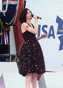 A British woman stands on a stage, wearing a black dress and holding a microphone in her left hand.