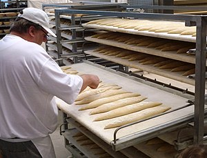 Baguette - A baker prepares baguettes for cooking
